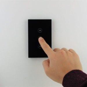 Llave dimmer negra inteligente WiFi TuyaSmart colocada en pared blanca, con mano accionando