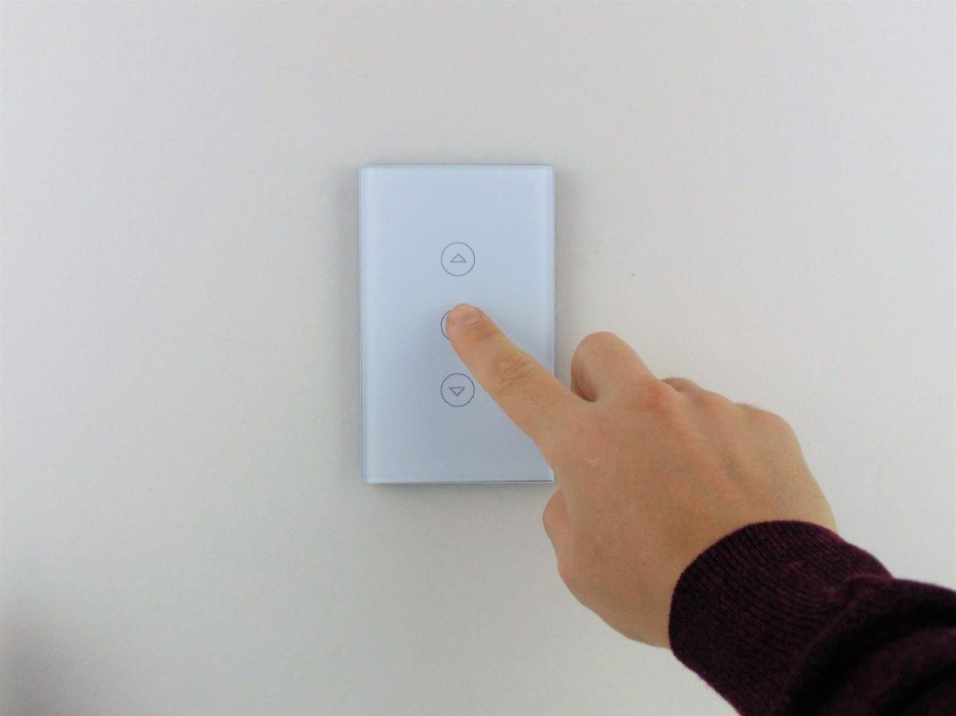 Llave dimmer blanca inteligente WiFi TuyaSmart colocada en pared blanca, con mano accionando
