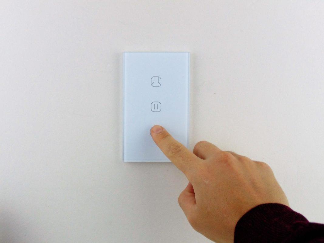 Llave de cortinas inteligente WiFi TuyaSmart colocada en pared blanca, con mano accionando