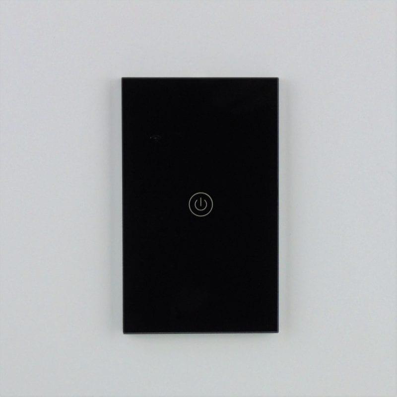 Llave inteligente WiFi TuyaSmart negra de una tecla, colocada en pared blanca