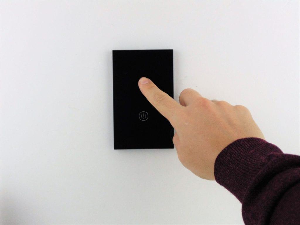 Llave inteligente WiFi TuyaSmart negra de dos teclas en pared blanca, con mano accionando