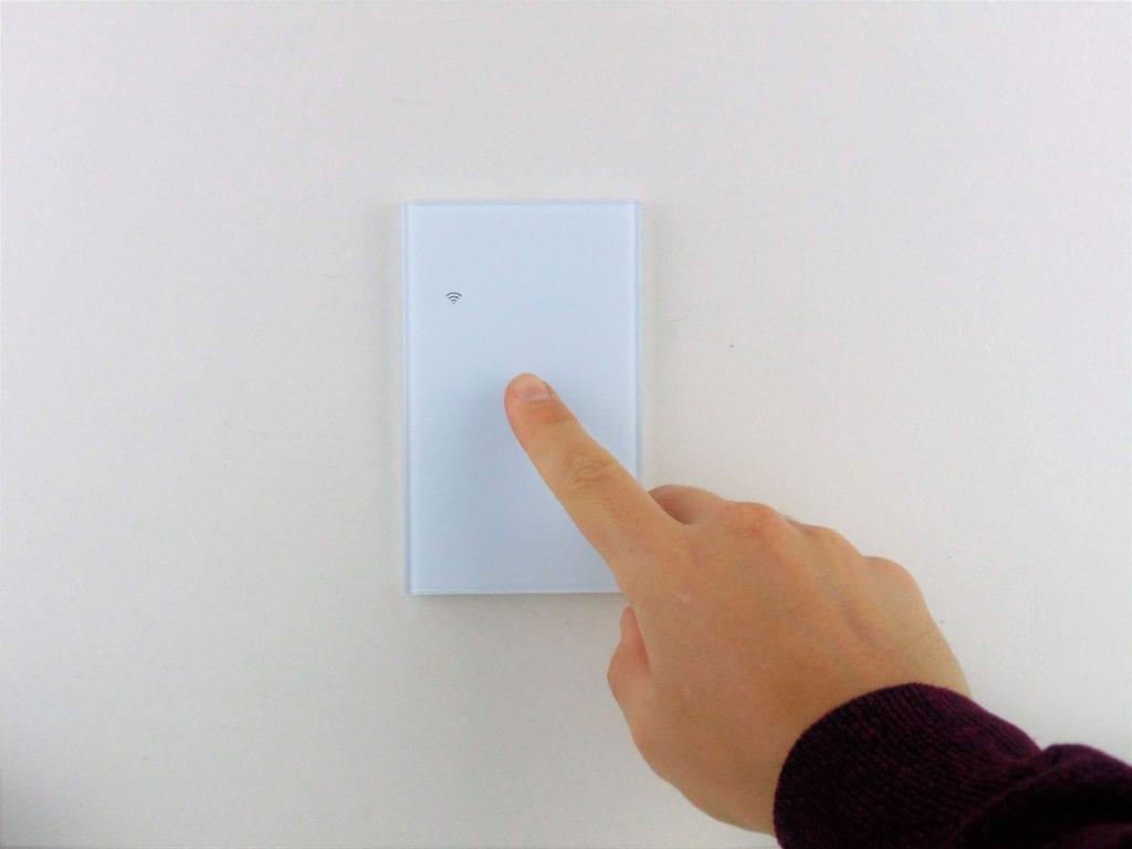 Llave inteligente WiFi blanca de una tecla, TuyaSmart, en pared blanca con mano accionando