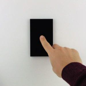 Llave inteligente WiFi TuyaSmart negra de una tecla, colocada en pared blanca, con mano accionando