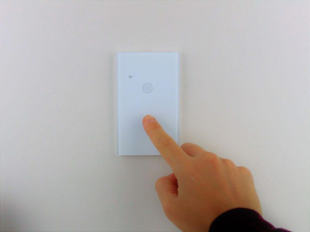 Llave inteligente WiFi TuyaSmart blanca de dos teclas colocada en pared blanca, con mano accionando